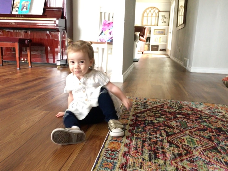 toddler sitting on floor in entryway of house