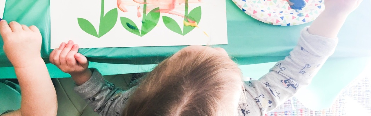 Top of toddler's head, painting a picture of flowers