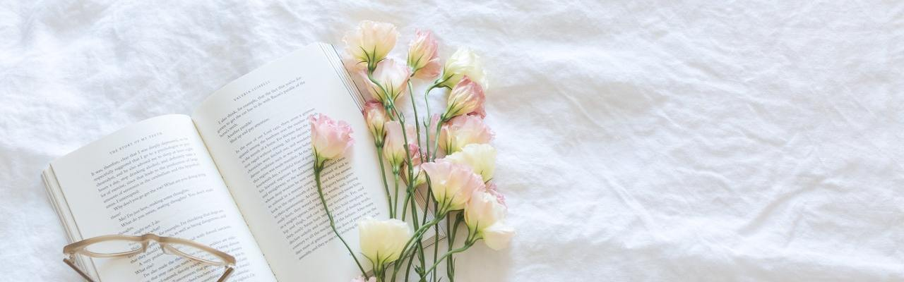 Open book with glasses and flower bouquet